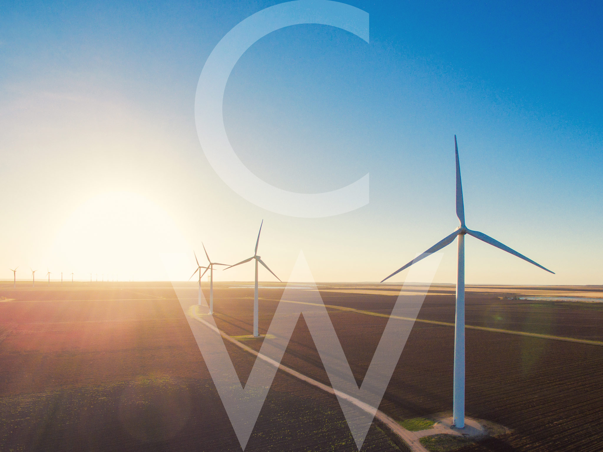 This is a landscape image of a wind farm at sunset.